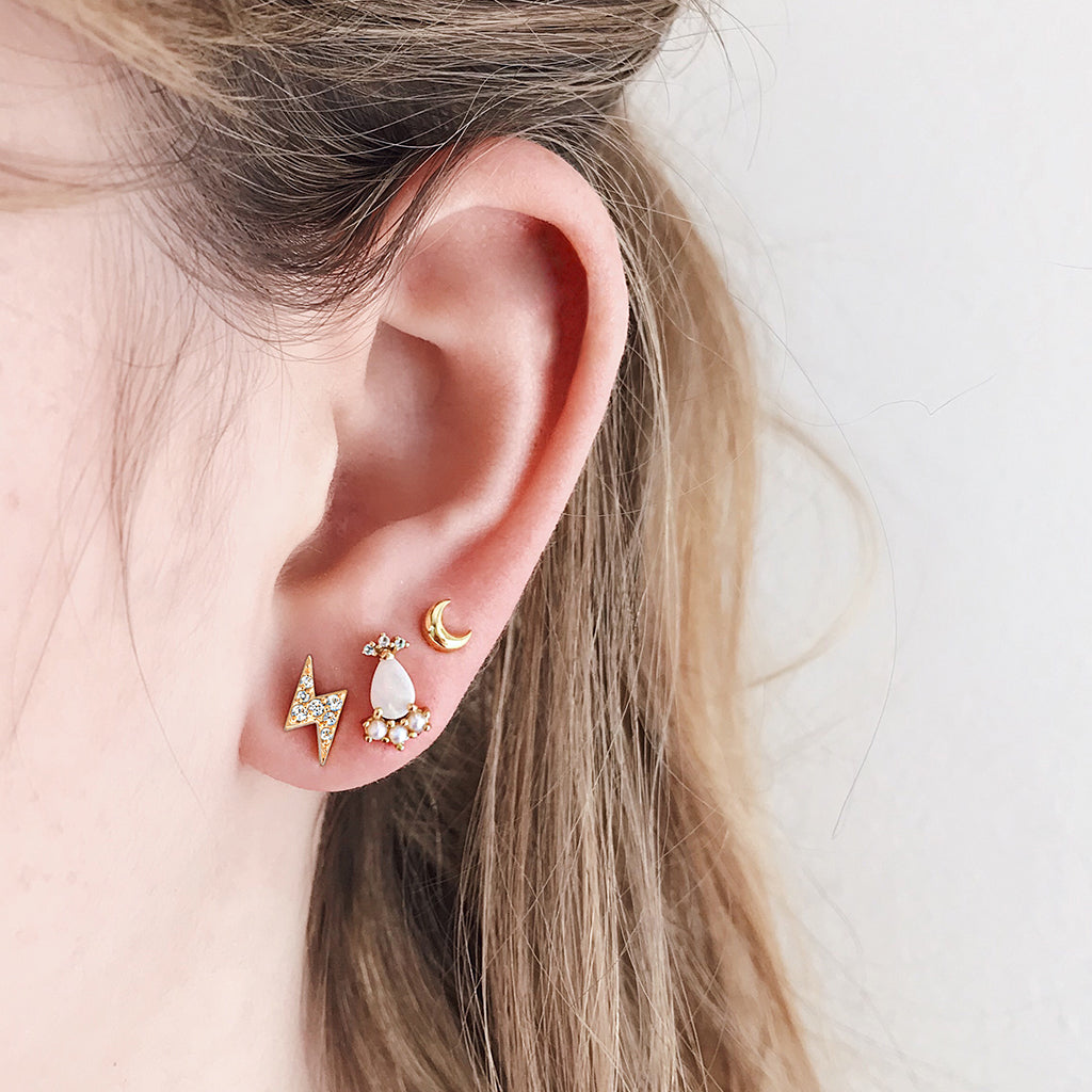 how to wear multiple earrings - gold lightning bolt pave ear studs mix with white opal diamond pearl earrings and tiny gold moon - beautiful magical cosmic statement stack on ears