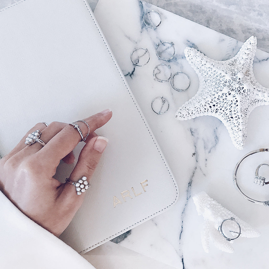 Jewellery flatlay - Stacking ring jewelry trend - Mix and match silver fine rings, pearl rings and diamond rings to create a modern stack - So fashionable and on trend - all white jewellery trend on white coral starfish with white grey marble in a minimalist jewelry display