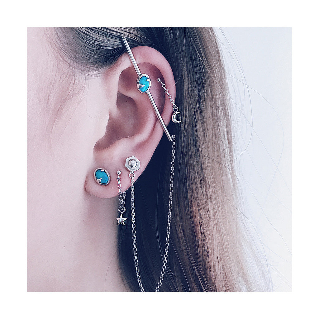 modern blue opal ear cuff bar with fine dangling chain and silver star and moon earrings worn in a modern futuristic combo