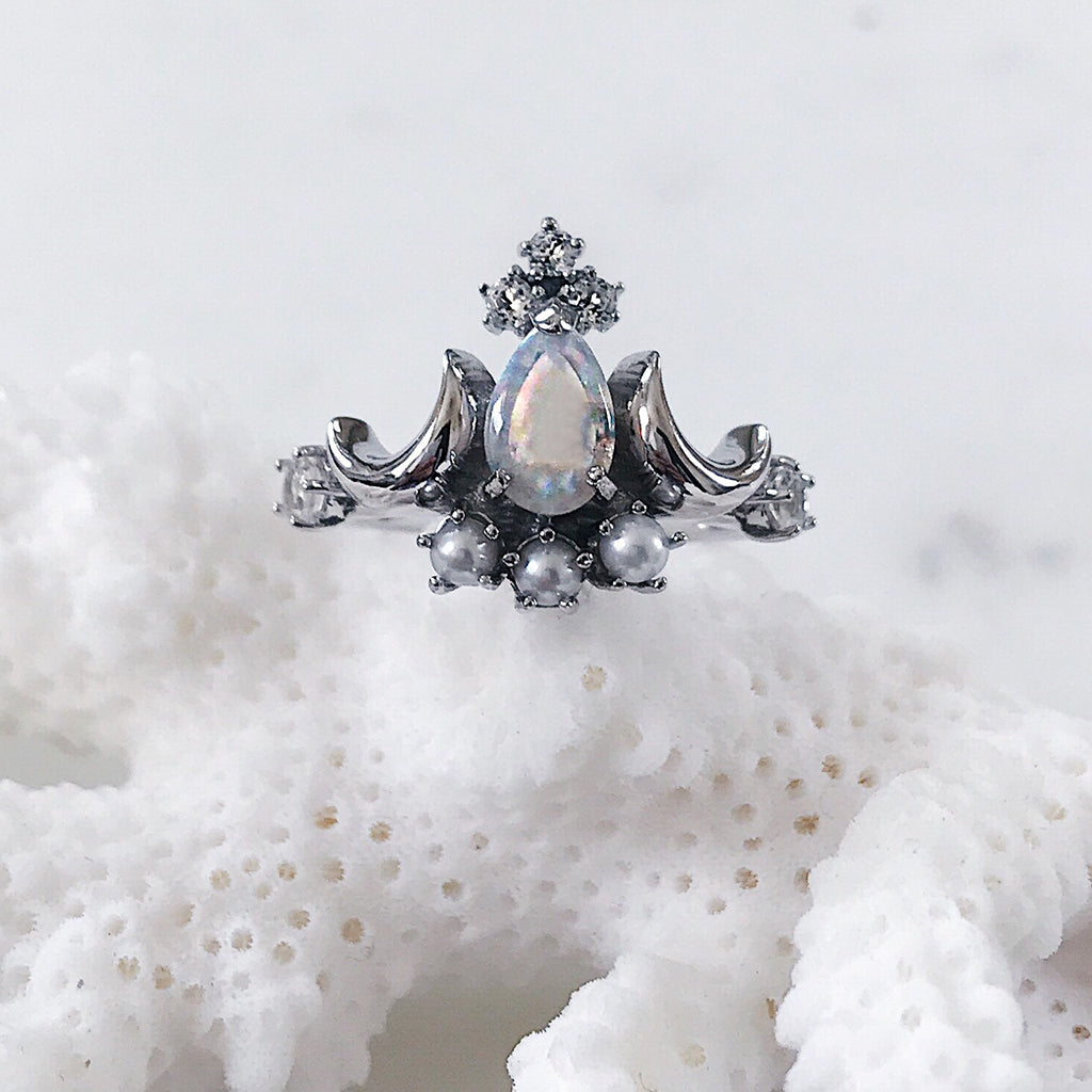 tiara ring with moody white Australian opal, dove grey pearls and sparkling grey diamonds flanked by two waning moons resting on a white coral - beautiful pagan silver ring for the luna goddess and those who worship the moon