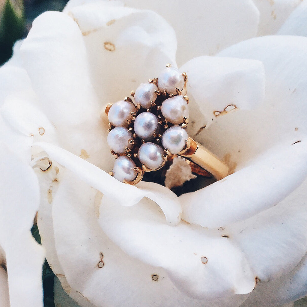 gold ring with luminous pearls in antique heritage diamond setting resting in a white rose