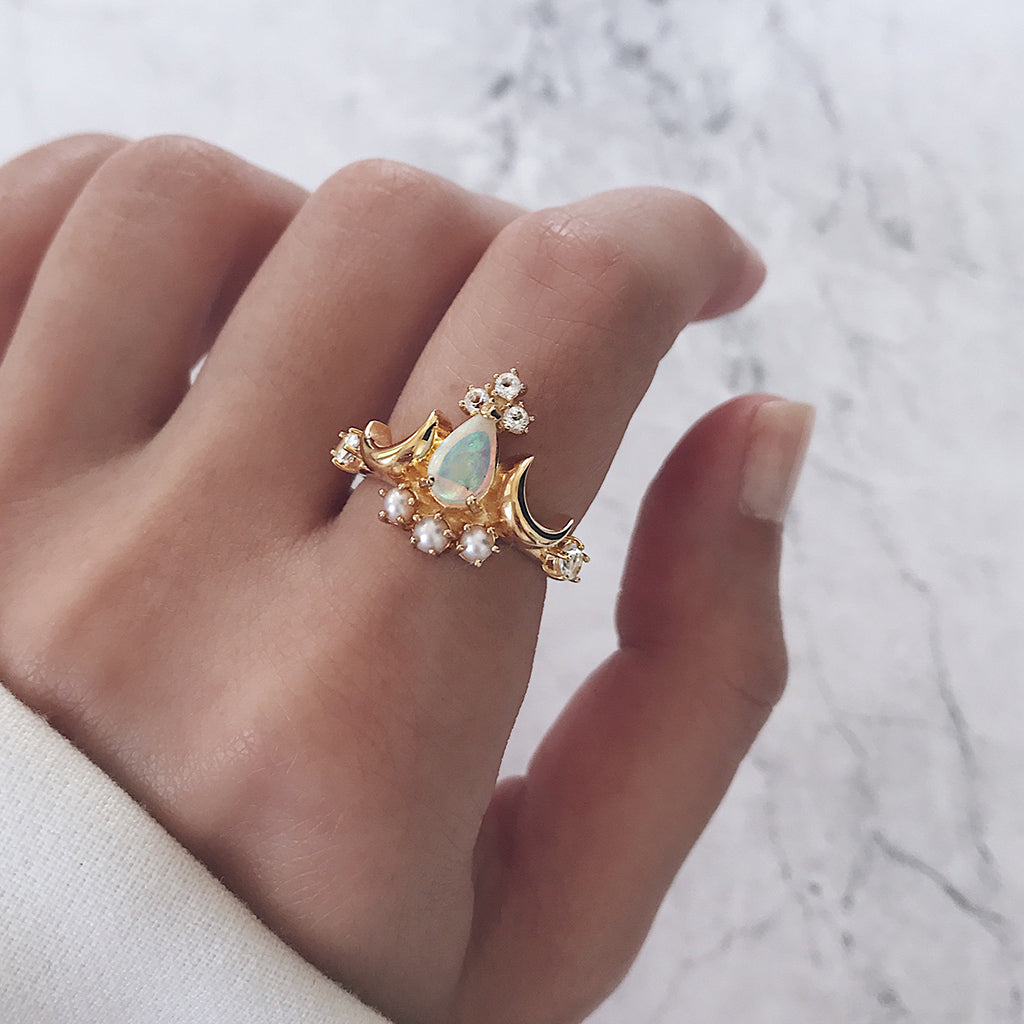 pear cut or teardrop cut white opal ring flanked by two crescent moons, topped with white diamond topaz and cream pearls in a beautiful gold tiara crown ring design - statement cocktail ring