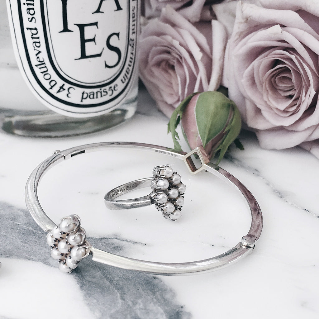 matching pearl cluster ring and bangle set. luminous fresh water pearls hand-set into a diamond shape heritage antique setting. sterling silver. resting on white marble with diptyque candle and tea roses