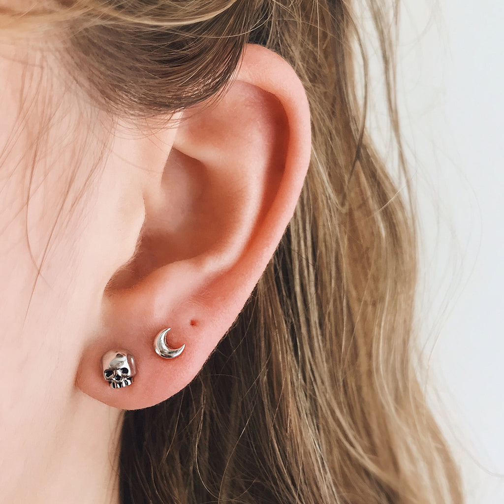 small skull stud earring sterling silver worn with small moon ear stud in 925 sterling so dainty skull jewelry