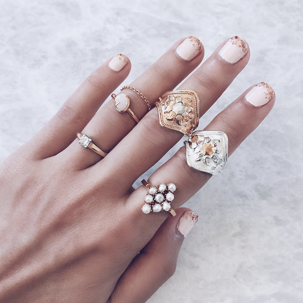 pearl cluster ring worn with other gold and silver sun and white opal rings in a beautiful combo