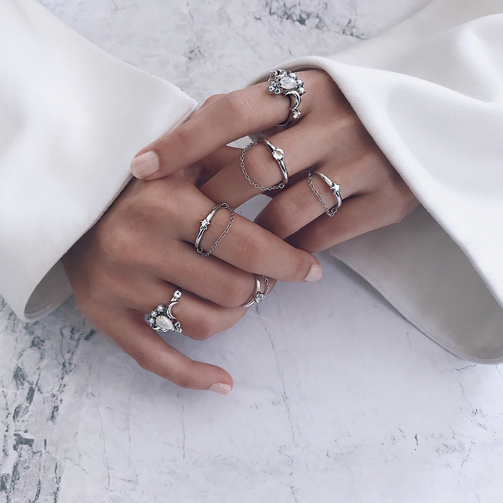 minimal ring stack of silver stacking chain rings, white opal teardrop cut pear shape rings and star chain rings - minimal jewellery trend, for those who love minimalist silver rings. Womens jewellery trend.