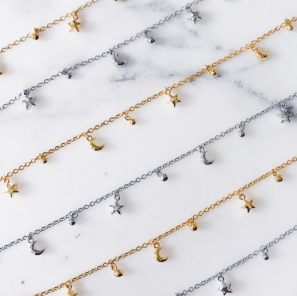 Stacks of star moon bracelets with tiny beads on a fine chain in 14k gold and sterling silver display on white marble. Gorgeous and modern bracelet women's jewellery designs
