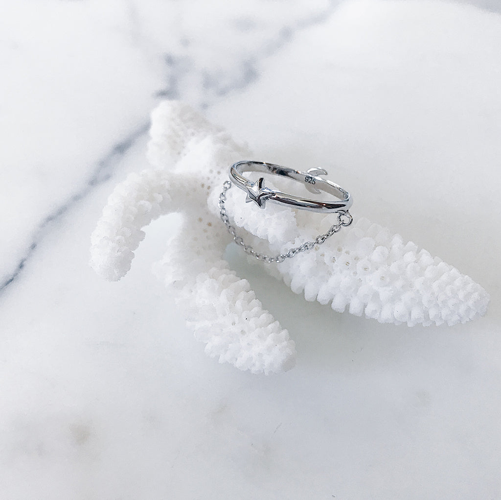Jewellery flatlay - Silver star ring with fine chain on a white coral and marble display - Clean, simple, classic