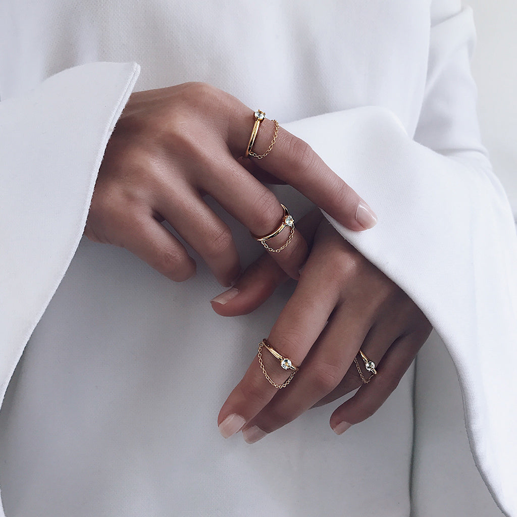 how to stack your rings in a minimal simple fashion - fine gold chain solitaire diamond rings layer together on base or midi fingers to create a dazzling diamond display - perfect gifts for bride or valentine's day