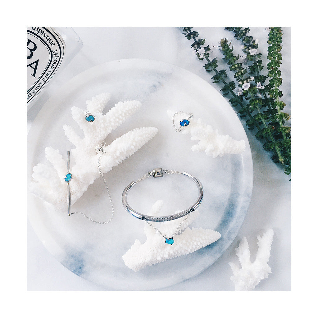 beautiful combo set of blue opal silver bangle, ring and ear cuff resting on white coral