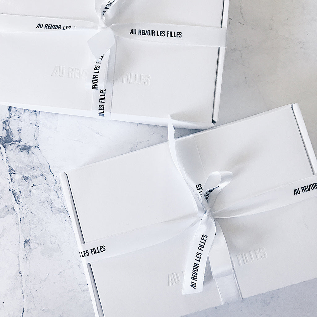 all white aesthetic. all white packaging and design box ideas from jewellery label AU REVOIR LES FILLES. white box with white embossed logo on white marble with black and white ribbon. minimal, monochrome designer packaging ideas.