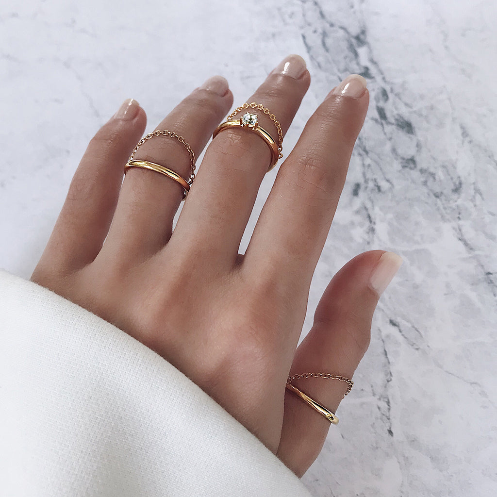 simple gold rings stacked in an elegant minimal way - fine gold bands with a hanging chain add texture and movement to fingers, highlighted by a sparkling white topaz diamond solitaire. for women who love minimalist jewelry and classic rings
