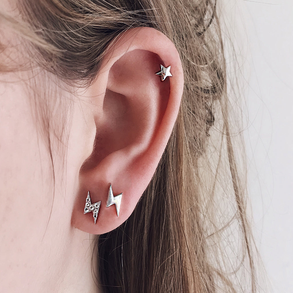 lightning bolt pave ear studs worn as a pair, mixed back with tiny star earring in sterling silver plated in rhodium. hypoallergenic and perfect for sensitive ears