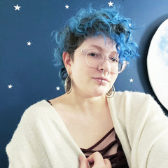 White female appearing person with curly short blue hair, large round light colored glasses, a septum ring and a lip ring is wearing a black top with a white open sweater. Their head is tilted to the right as they look into the camera. They are standing in front of a blue wall with white polka dots.
