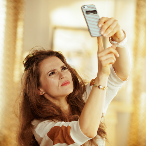 woman trying to get a signal on her cell phone
