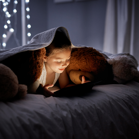 child using a tablet in bed