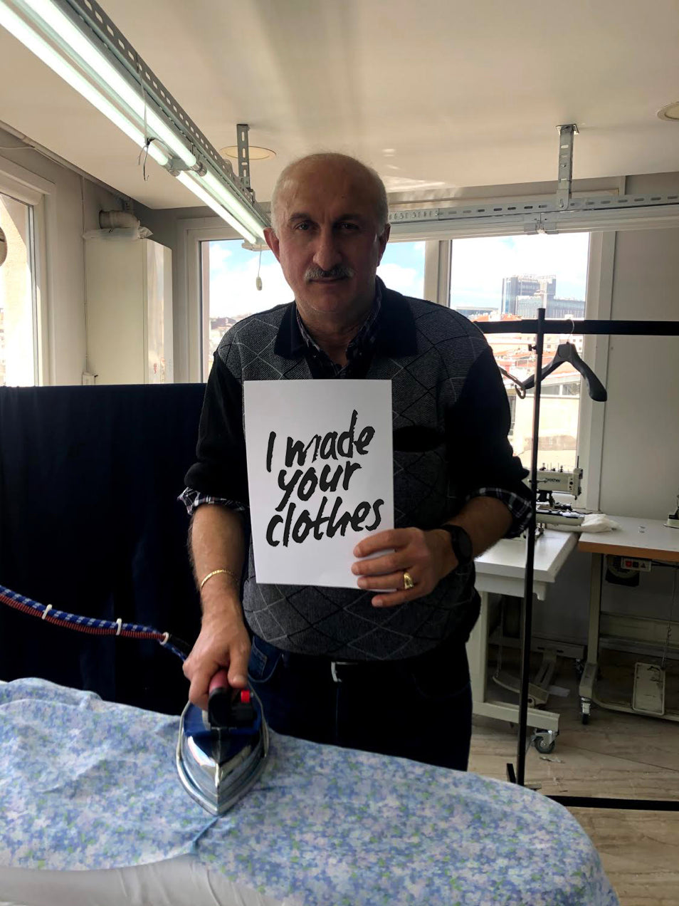 clothing factory, male worker holding fashion revolution sign