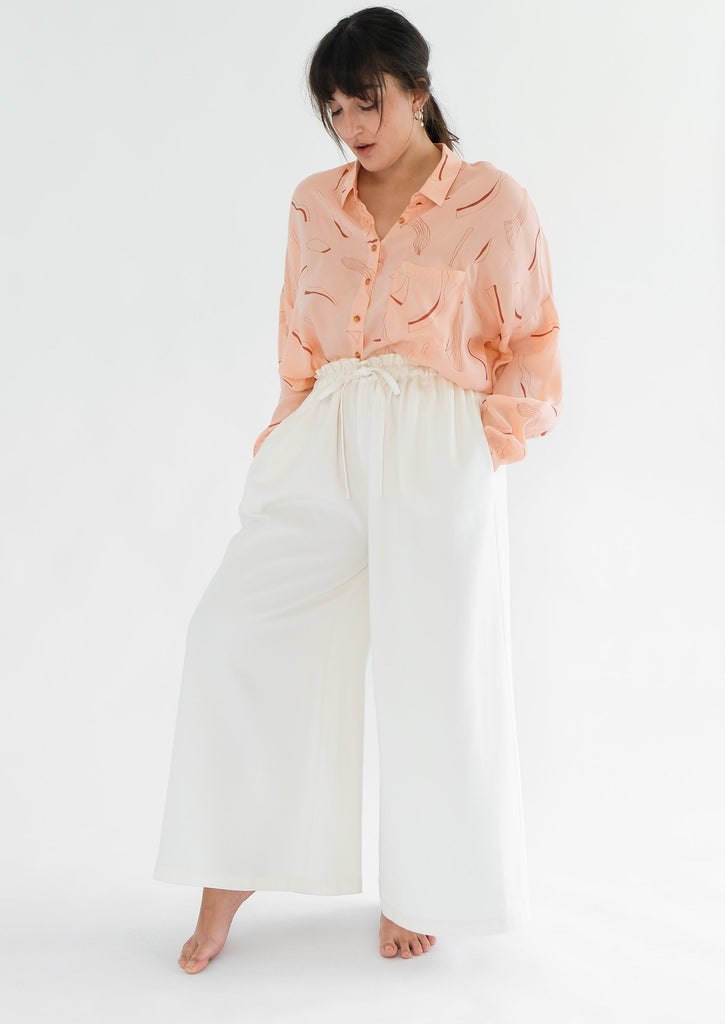 Girl standing pink silk printed shirt and white trousers
