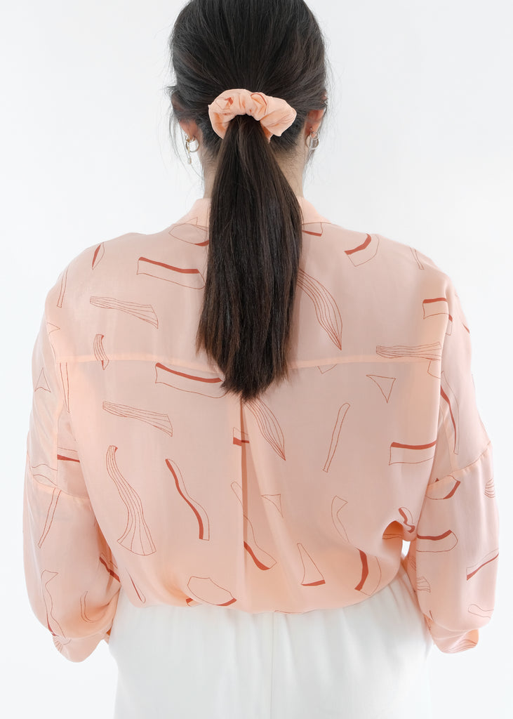 Girl standing backwards wearing pink silk printed shirt