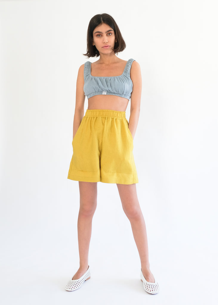Girl standing wearing blue top and yellow shorts