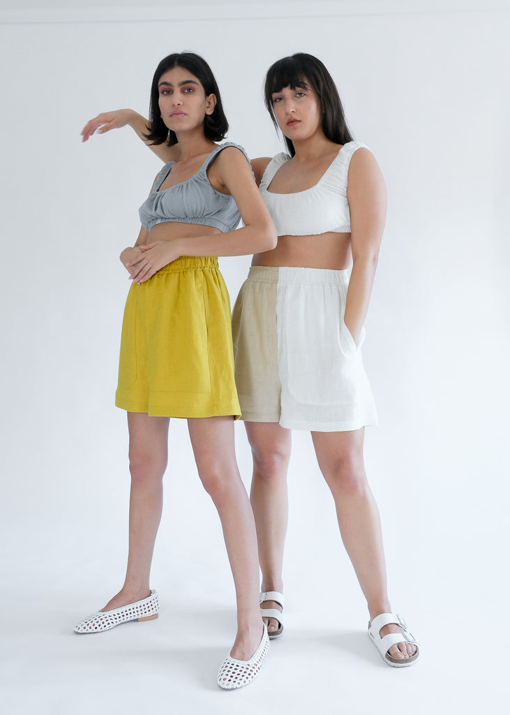 Two girls standing wearing blue and white tops with yellow shorts
