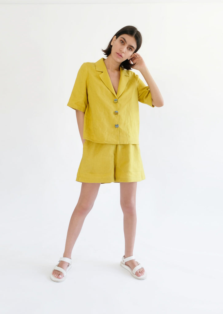 Girl standing wearing yellow shirt and shorts