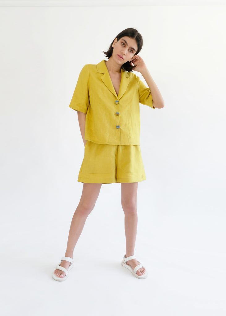 Girl standing wearing yellow shirt and shorts set