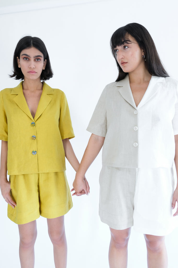 Two girls holding hand wearing yellow shirts and shorts