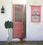 Good Vibes Only Flag hung on white brick house with pink door and labradoodle puppy