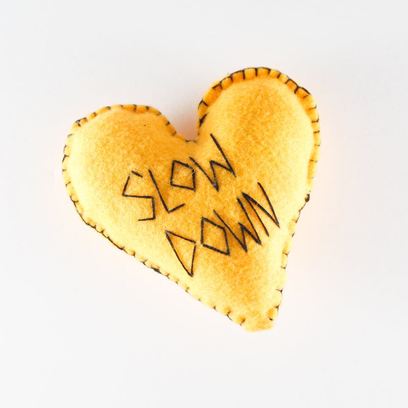 "Felt heart hand stitched with the words ""slow down""by Annie Lou Studios"