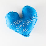 "Felt heart hand stitched with the words ""you're smothering me""by Annie Lou Studios"