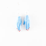 Clay Hand Earrings by Anjelica Colliard in light blue with red nails