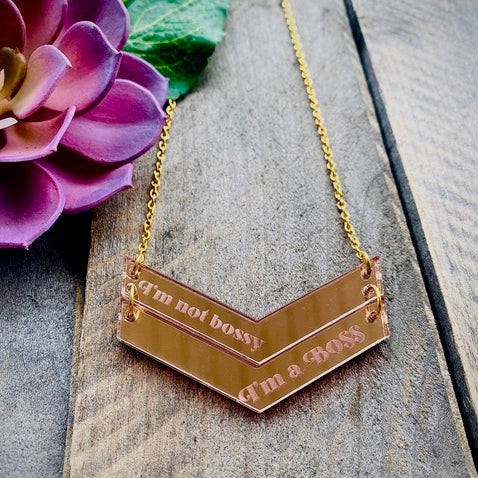 International Women's Day Necklace by PolyPaige. Pink and gold text chevron pendant on a nickle free chain gold colored chain that reads I'm a BOSS.