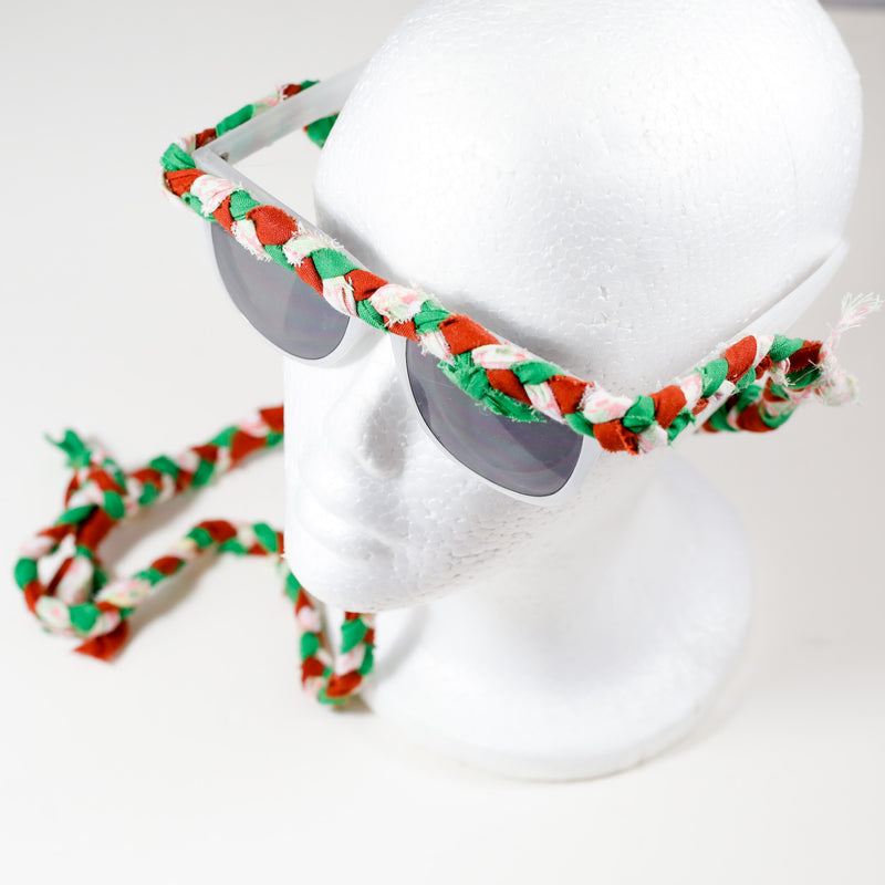 tri color (green, red, white) braided sunnies by stella g on a white foam head display