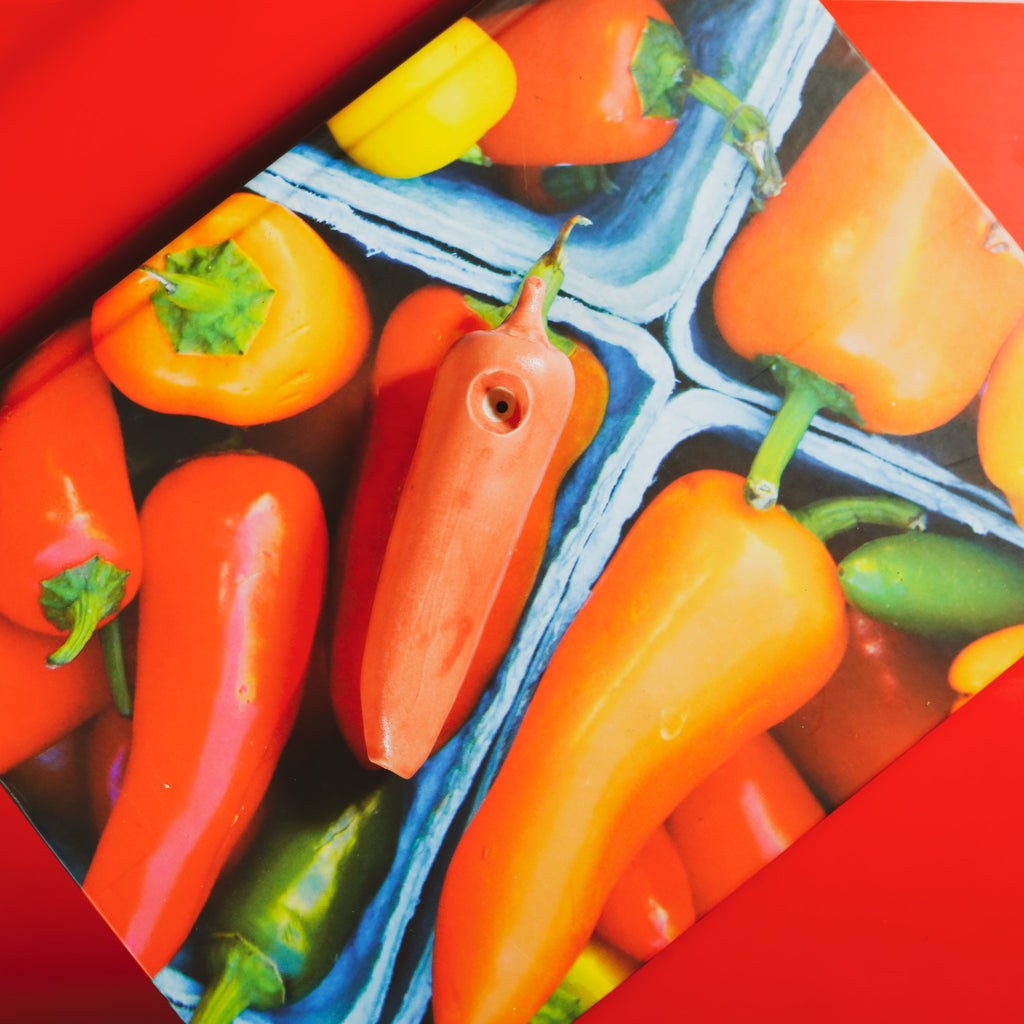red pepper ceramic pipe by ficus ceramica on top of a cookbook cover with peppers in front of a red background