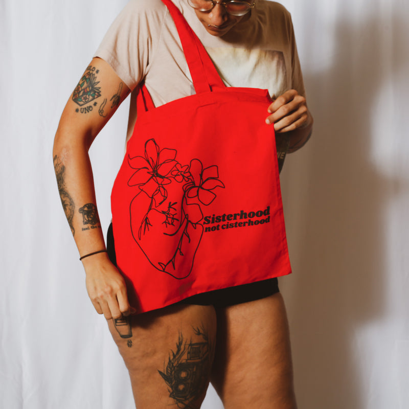 sisterhood not cisterhood tote bag as modeled by a person peeking at the design, infront of a white background