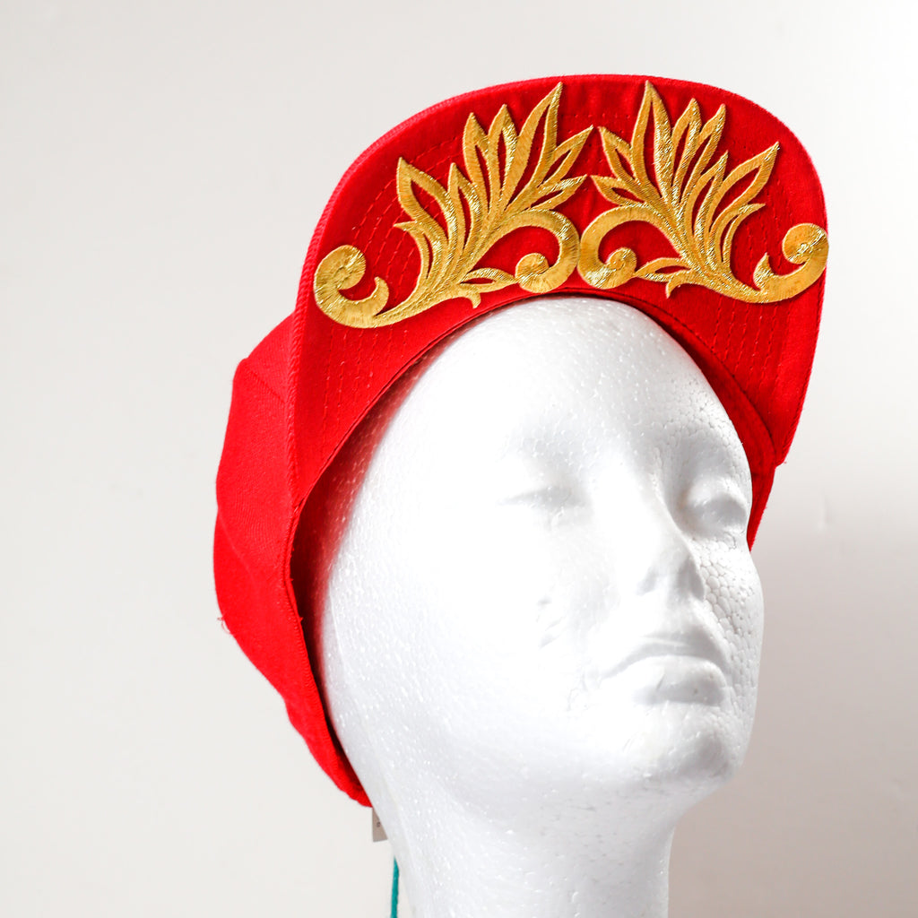 Red snap back hat with gold thistle