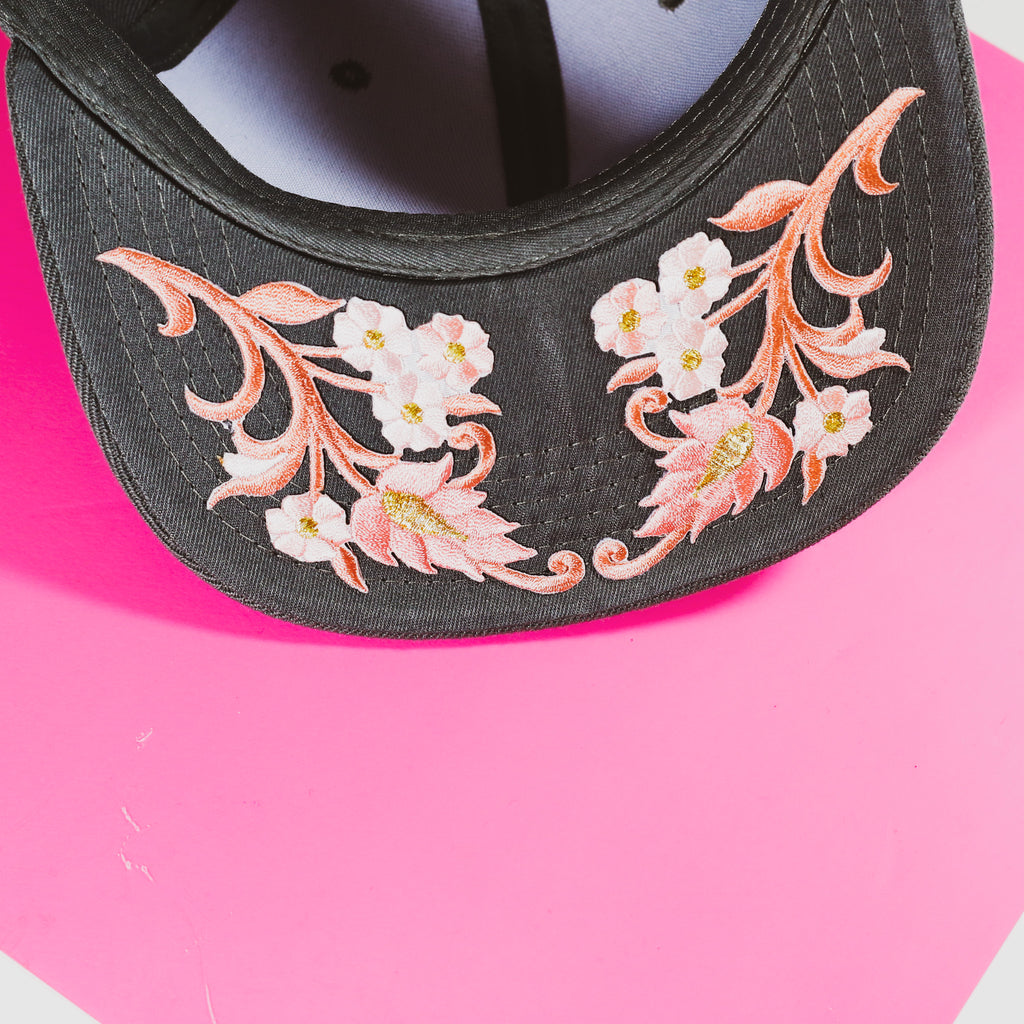 Dark grey snap-back hat with pink thistle
