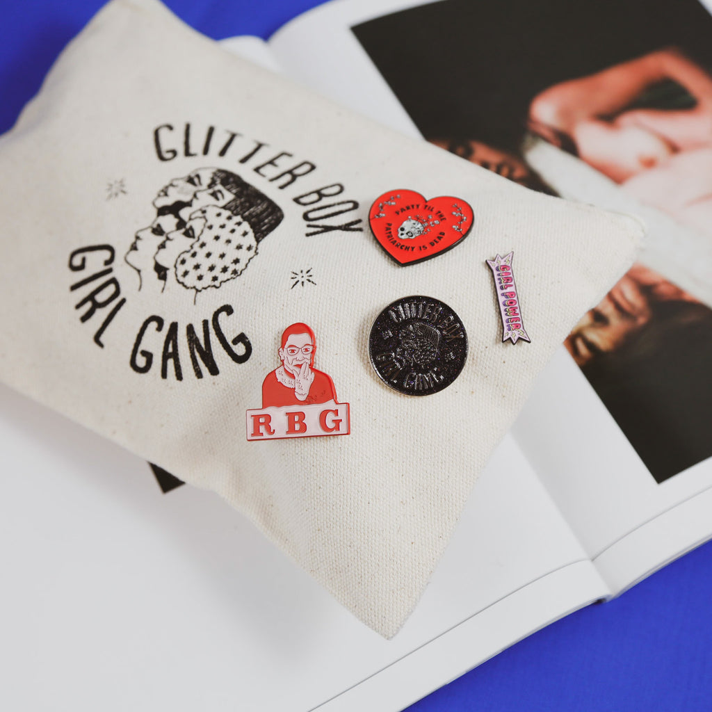 enamel pins by the glitter box gilr gang on make up pouch