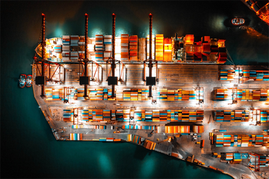 A cargo ship unloading containers at night
