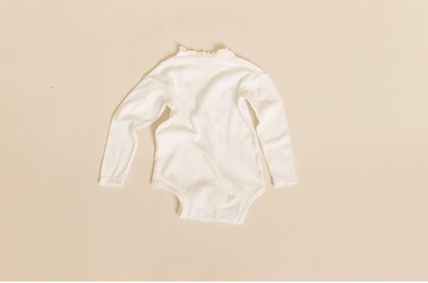 Frill neck onesie in milk
