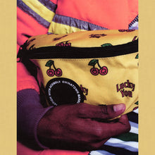Close up of Acembly X Chinatown Market Lucky Waist Pack fabric, with 'Lucky You' text and red cherries
