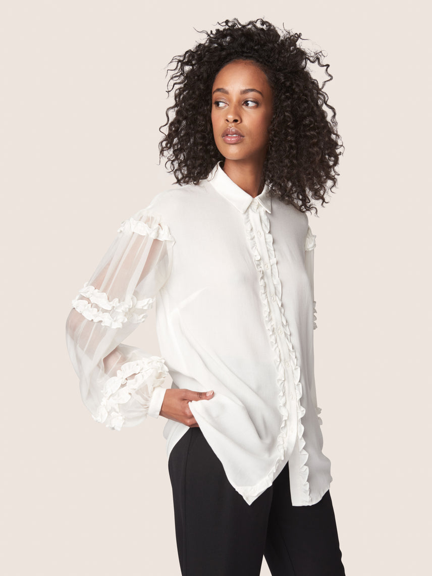Sheer blouse with ruffled bishop sleeves and ruffled front button closure