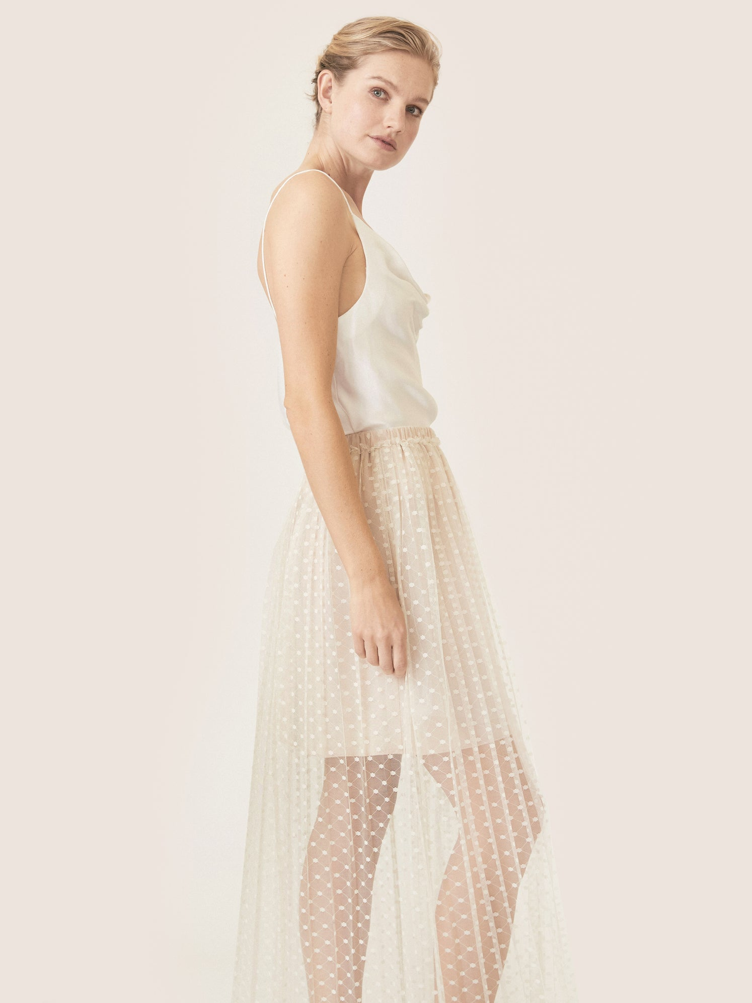 Side view of high waisted pleated skirt with dotted lace fabric.