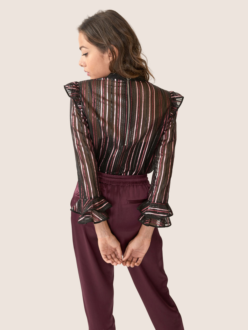 back view of metallic striped red, pink, and blue sheer organza blouse with a front tie and ruffles