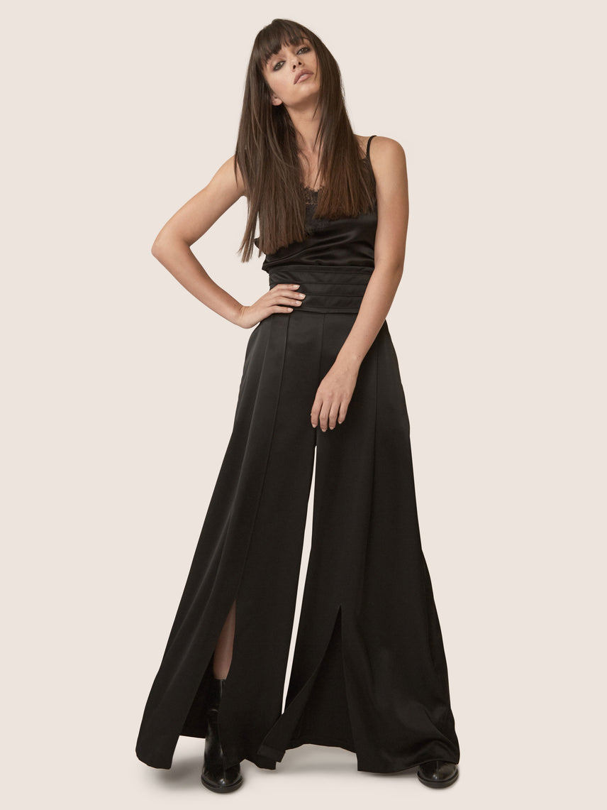 Contemporary black satin wide leg pants with ultra-high waistline and front slit.
