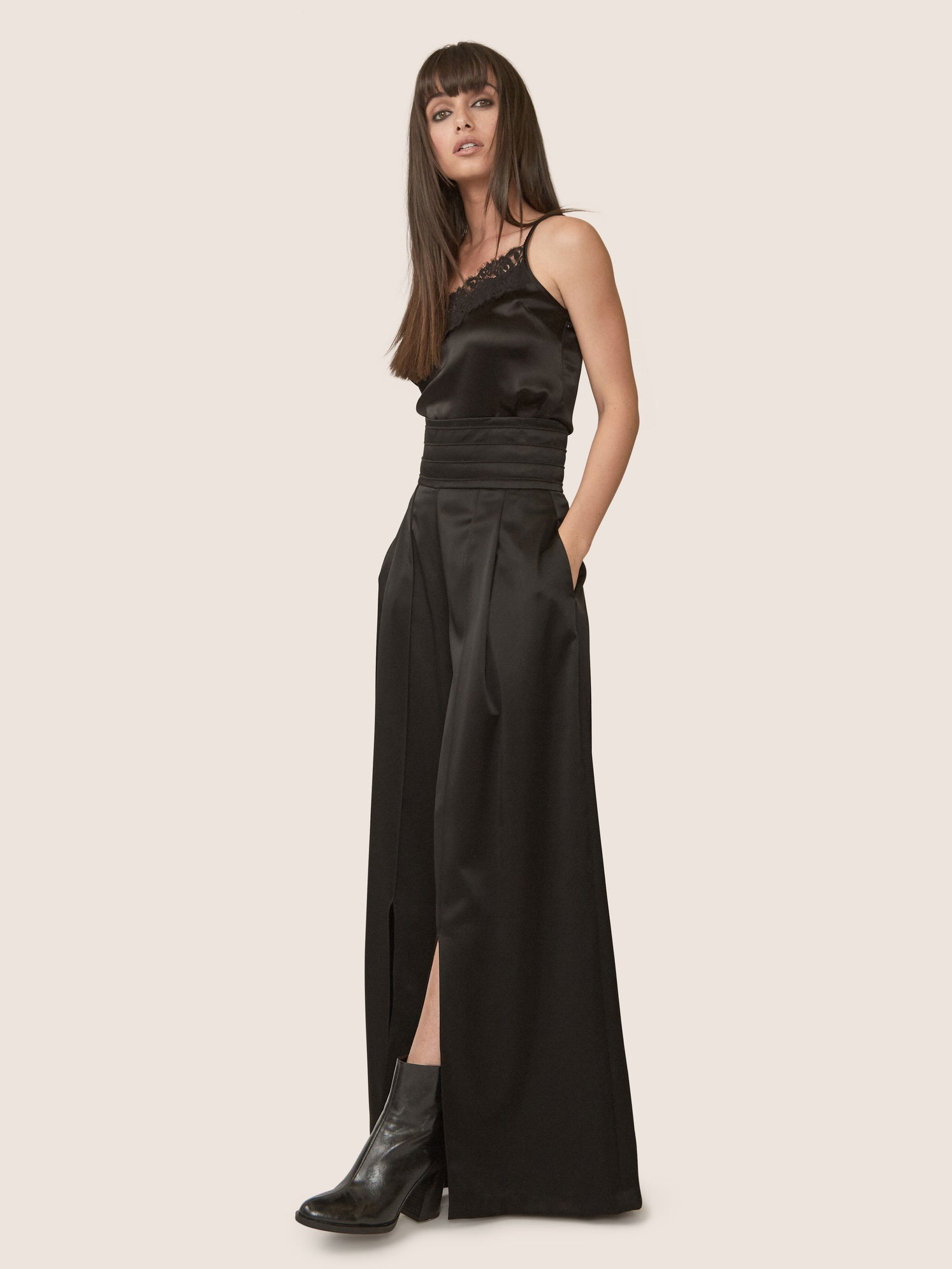 Side view to show off front slit of contemporary black satin pant with ultra-high waistline.