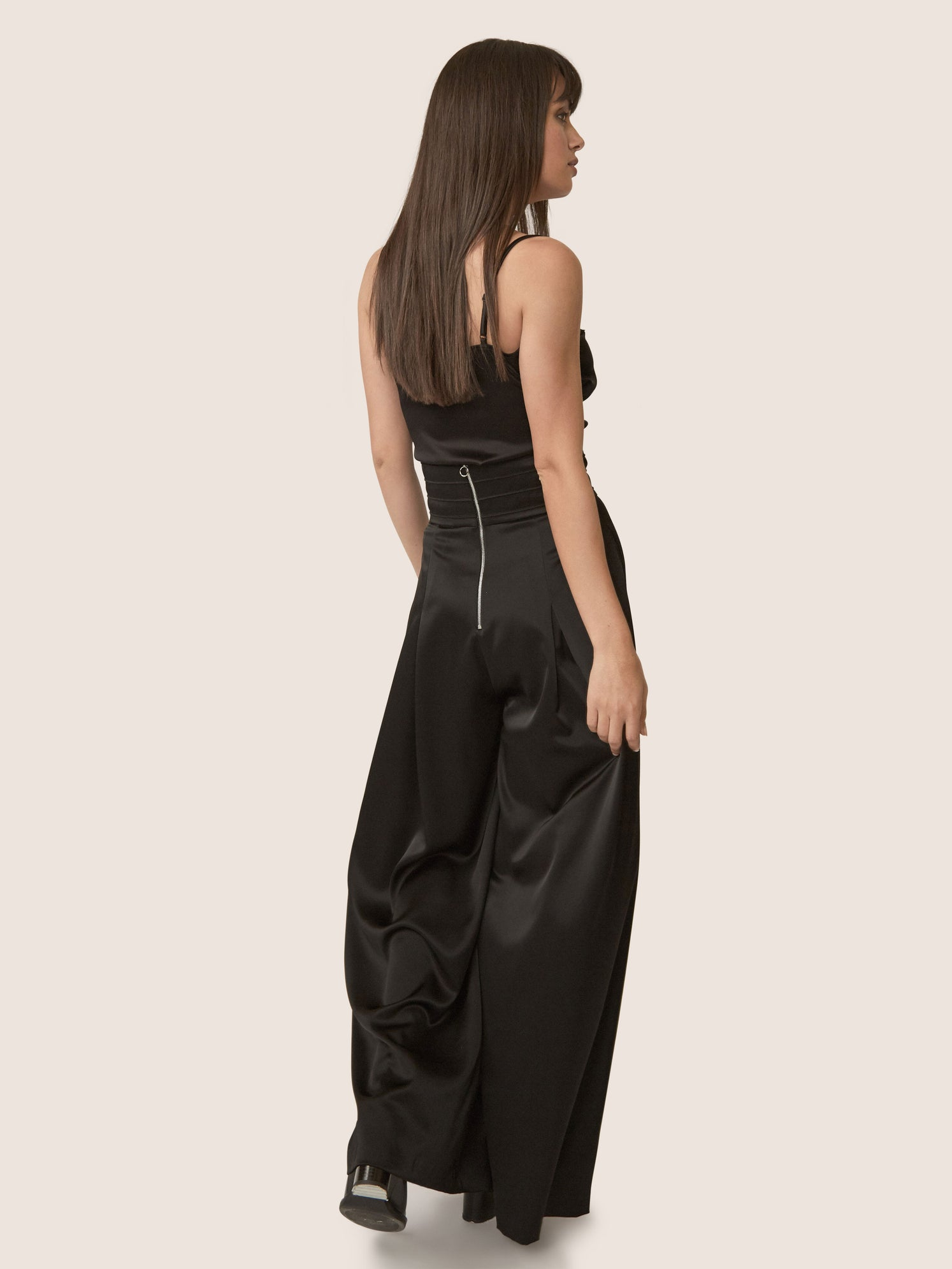 Back view of contemporary black satin wide leg pant with ultra-high waistline and front slit.