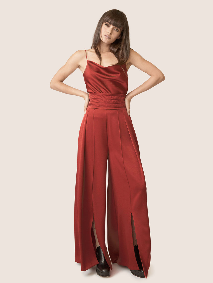 Full body image of contemporary rust satin wide leg pants with ultra-high waistline and front slit.