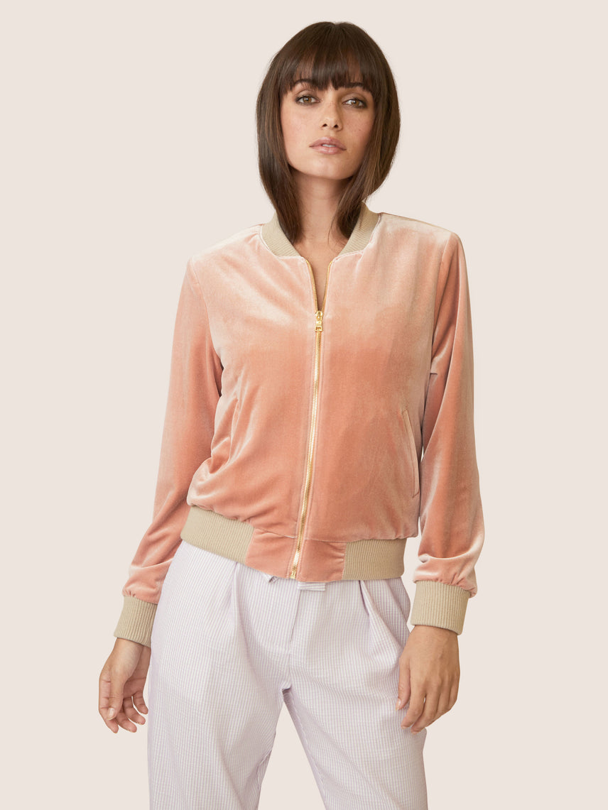 Front view of zipped peach velvet bomber jacket with side pockets.